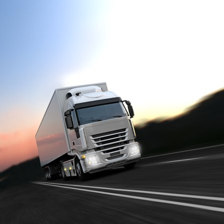 A white truck driving on the highway with the sunset in the background