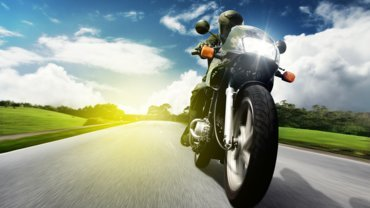 Black Motorcycle on its way on the road with the sun and green grass in the background