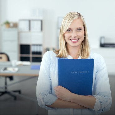 Pretty Blond Young Office Woman Hugging a Blue Documents Folder and Smiling at the Camera Inside the Office.