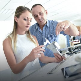 Young blond woman in engineering training class and teacher