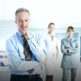 Businessman with confident pose in the office and his team in the background