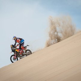 KTM Rally Dakar Rider cruising down an abrupt sand dune leaving smoke and sand cloud behind