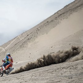 KTM Rally Dakar Rider rear view of riding to the left on sandy dune