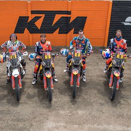 6 KTM Rally Drivers looking happy and standing on their Motorcycles with big KTM logo painted on garage door behind