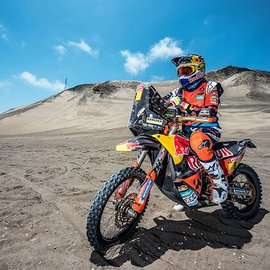 KTM Rider a the Rally Dakar standing on the Motorcycle on rocky sandy grounds