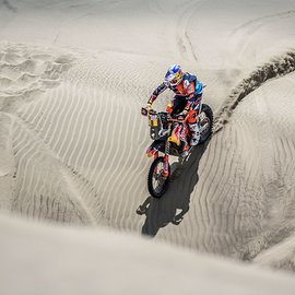 KTM Rider at the Rally Dakar driving over silver beige sand dunes leaving trails behind