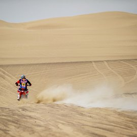 KTM Motorcycle Rider in the middle of the desert wirth sand dunes all around at the Rally Dakar 2018