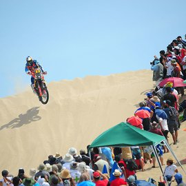 KTM Driver on KTM Motorcycle jumping over sand dunes in front large public under colorful umbrellas